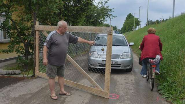 Ideiglenes kerítést és kiskaput kapott a Szőregi út 47. lakója, Filáry Jenő. A nyugdíjas férfi nem örül, hogy a szervizút zsákutca lesz, és megszűnik az egyik lehajtójuk. Fotó: Karnok Csaba, delmagyar.hu